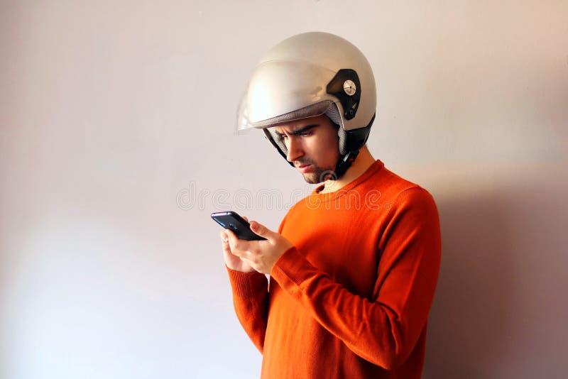Biker vestito di arancione e guarda il cellulare fotografie stock libere da diritti