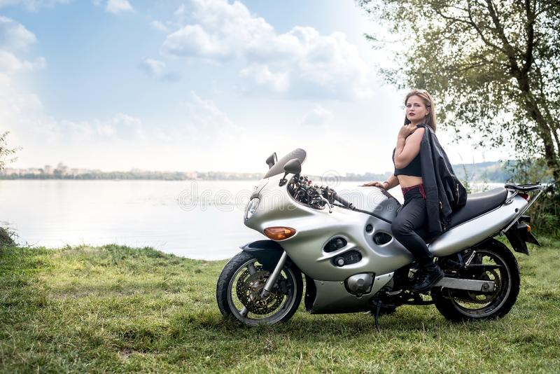 Biker woman with motorcycle rest near a pond royalty free stock images
