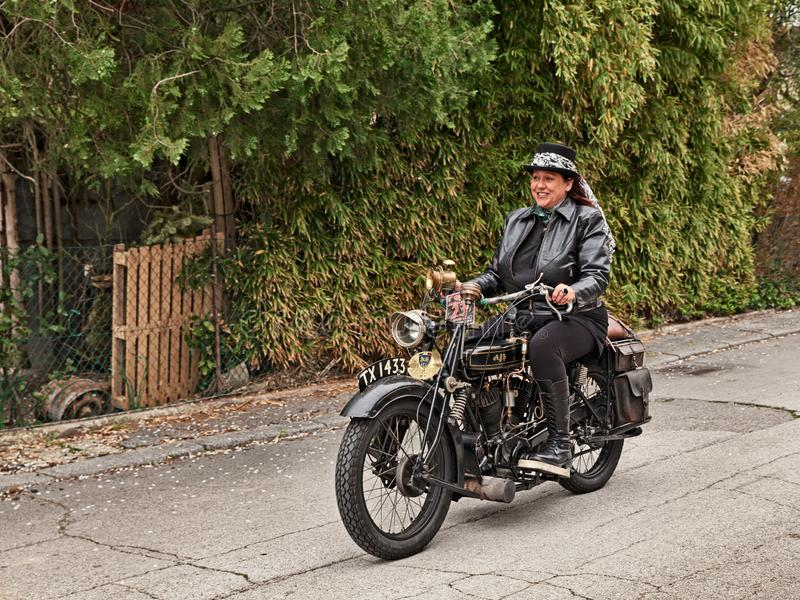 Biker woman riding classic motorcycle AJS G2 800 cc 1926. Biker woman riding vintage AJS G2 800 cc V-twin engine 1926 in classic motorcycle rally Circuito di San royalty free stock photo