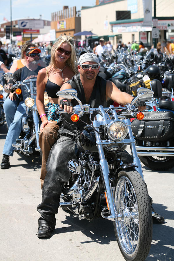 Bikers at Sturgis Bike Rally. Sturgis, South Dakota, USA - August 8, 2007: Man and woman cruising down Main Street on their Harley Davidson at the famous annual royalty free stock images