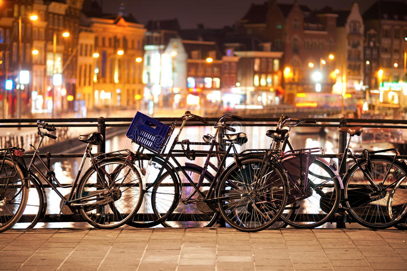 Bikes in Amsterdam. Bikes parked on a bridge at night in Amsterdam royalty free stock images