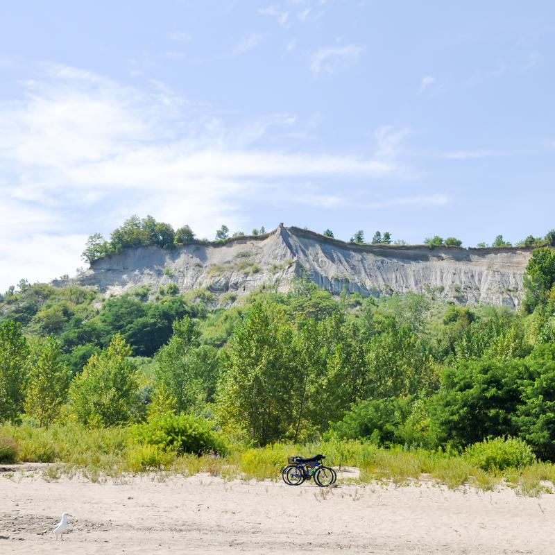 2 bikes on the beach with trees and cliffs in the background - Scarborough Bluffs - Toronto. Canada stock images
