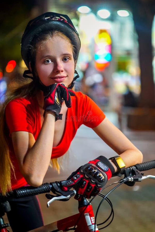 Bikes bicyclist girl wearing bicycle helmet. Outdoor night portrait. Bikes bicyclist girl wearing bicycle helmet. Outdoor portrait of happy teenager returns royalty free stock photos