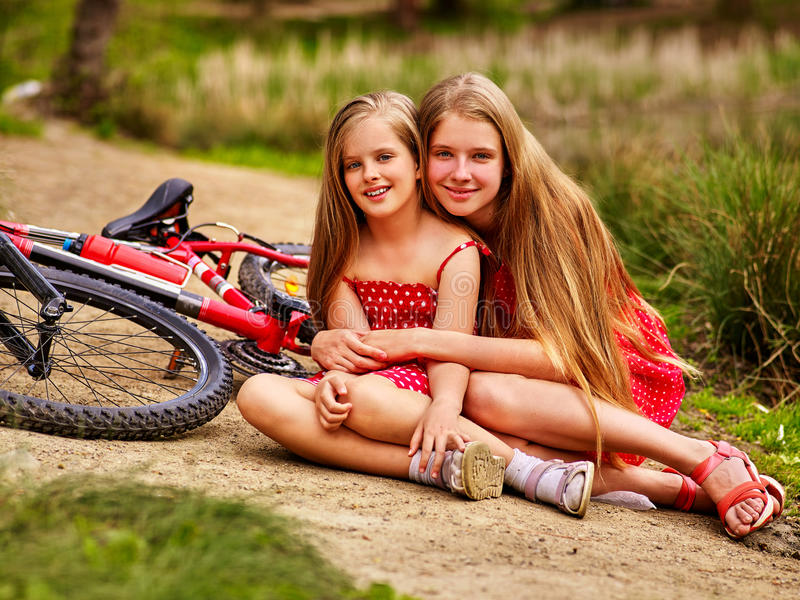 Bikes cycling children sitting road near bicycles. Bikes cycling children. Happy children are sitting on country road near bicycles. Cycle racing concept royalty free stock image