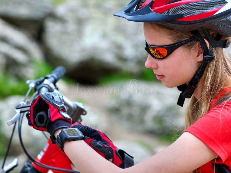 Bikes cycling girl. Bicyclist girl watch on smart watch. stock photo