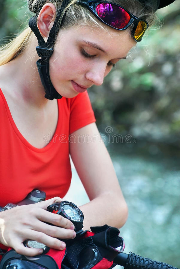 Bikes cycling girl. Bicyclist girl watch on watches. royalty free stock photography
