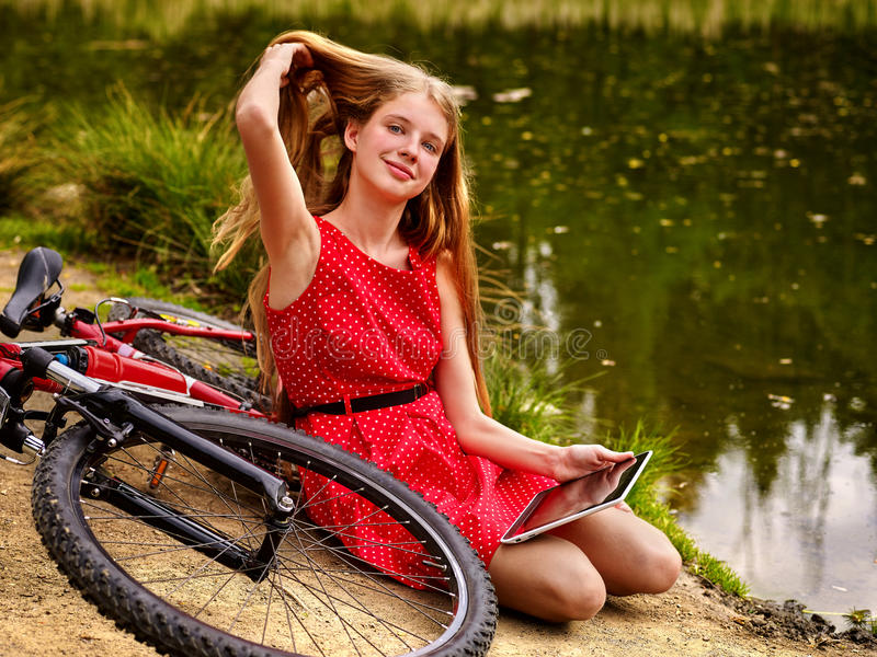 Bikes cycling girl. Girl has rest near bicycle into park. Bikes cycling girl. Girl wearing red polka dots dress has rest near bicycle into park. Children watch royalty free stock photo