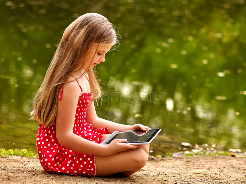 Bikes cycling girl into park. Children watch tablet pc. Bikes cycling girl. Girl wearing red polka dots dress recreation near bicycle into park. Children watch stock photos