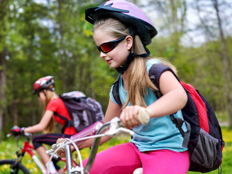 Bikes cycling girls with rucksack cycling in summer park. Bikes bicyclist girl. Girls wearing bicycle helmet and glasses with rucksack rides bicycle. Girls royalty free stock photo