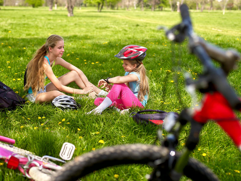 Bikes cycling girls wearing helmet. Girls have rest from cycling. Bikes cycling girls. Girls children rides bicycle. Girls have rest from cycling. Cycling is stock photo