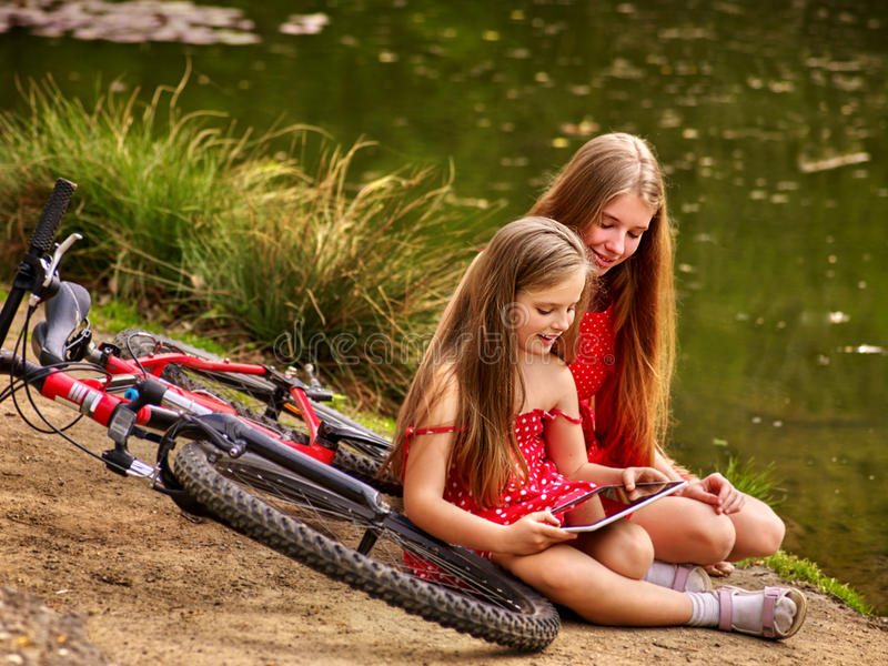 Bikes cycling kids. Girl recreation near bicycle into park. Children watch tablet pc. Girl in ecotourism. Older sister shows younger new game on tablet sitting stock photo