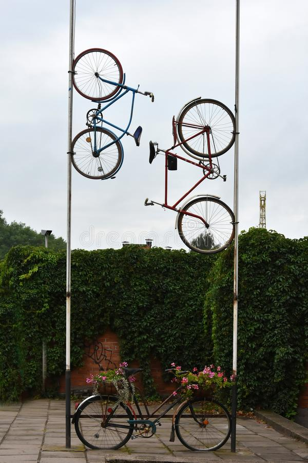 Two bikes up on a mast, eye catcher for a repair service. Bikes mounted high up on a mast, eye catcher for a repair service or a bike rental royalty free stock image