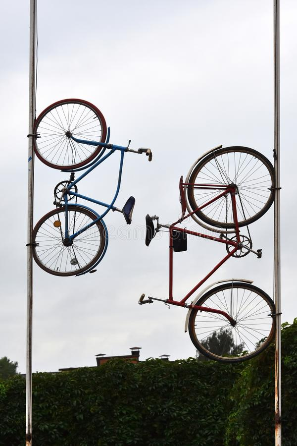 Two bikes up on a mast, eye catcher for a repair service. Bikes mounted high up on a mast, eye catcher for a repair service or a bike rental stock photo