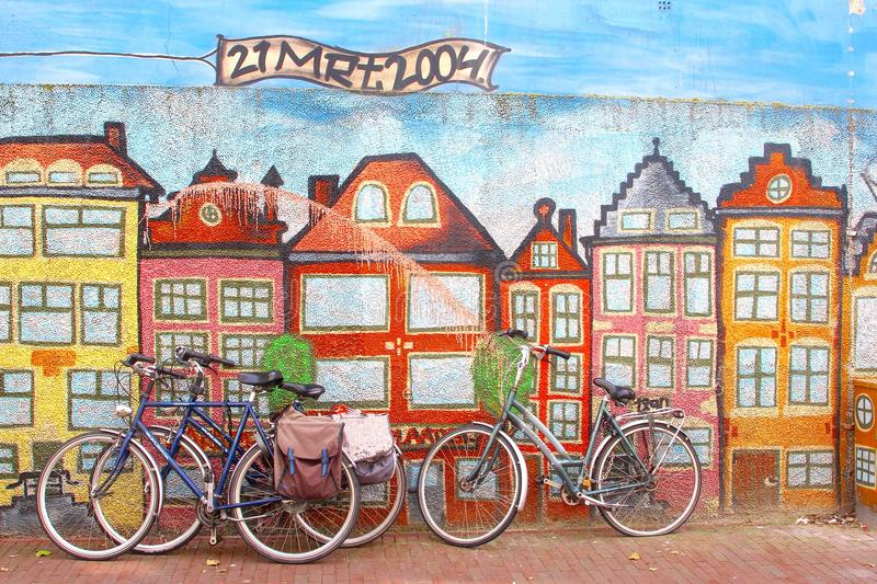 Bikes at a mural with canal houses in Amsterdam style, Netherlands. Bikes at a street art wall with Amsterdam style canal houses in Leeuwarden, Netherlands. In stock photo