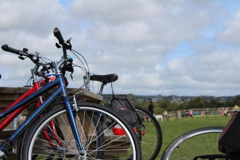 Bikes resting on a park bench, on a cloudy day stock images