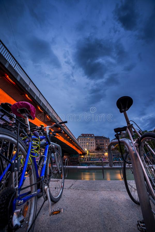 The bikes were parked in a bicycle parking lot next to the bridge on the Danube canal in Vienna. It`s dusk and the sky is very stock images