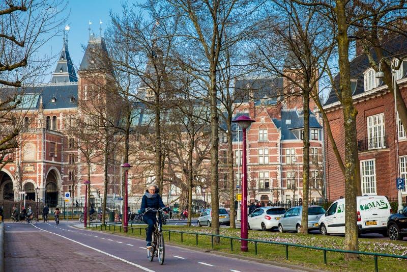 bikeway的骑自行车者在阿姆斯特丹旁边国家博物馆在一个寒冷早期的春日 图库摄影