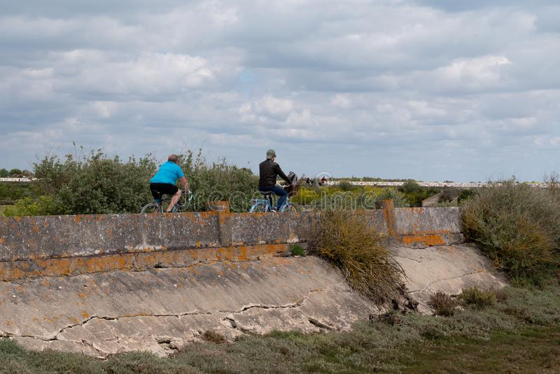 Biking couple Rides on a Bikeway across the sea in Ile de Re France stock photos