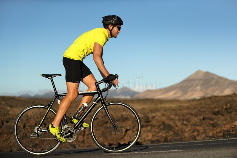 Biking cyclist male athlete going uphill on open road training hard on bicycle outdoors at sunset royalty free stock image