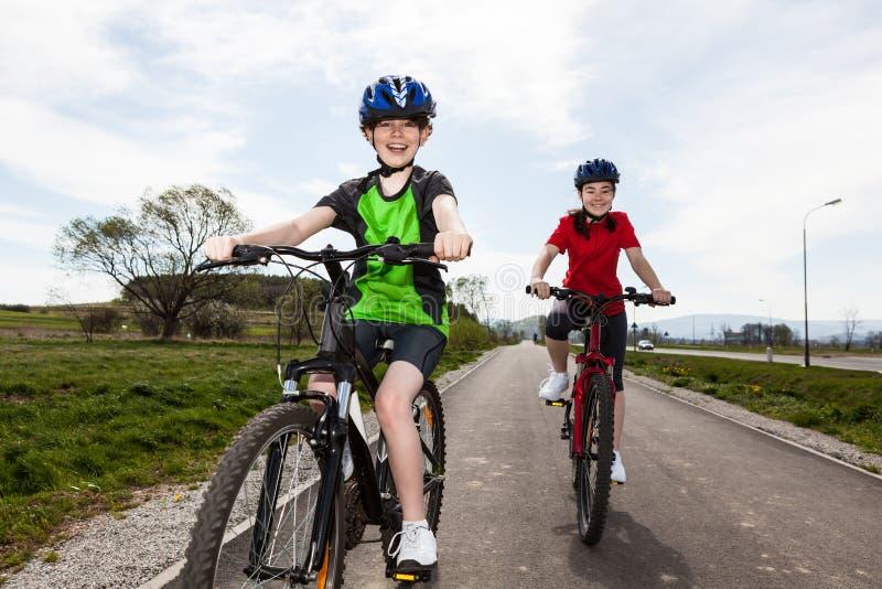 Biking da menina e do menino foto de stock
