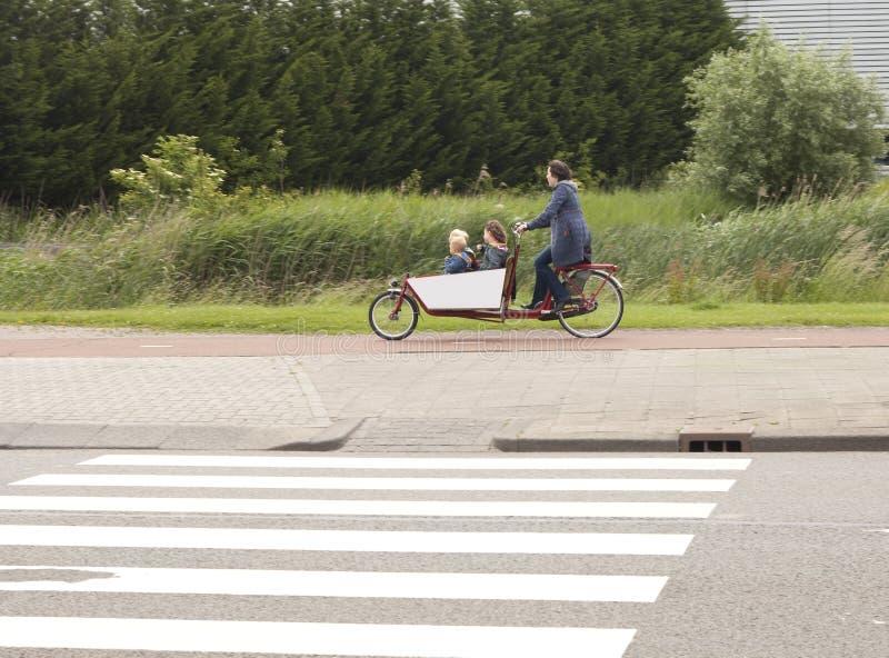 Biking a los niños a la escuela en los Países Bajos imágenes de archivo libres de regalías