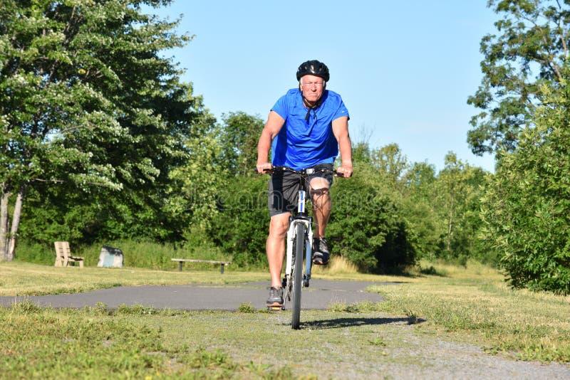 Biking sério de Retiree Male Cyclist do atleta imagens de stock royalty free