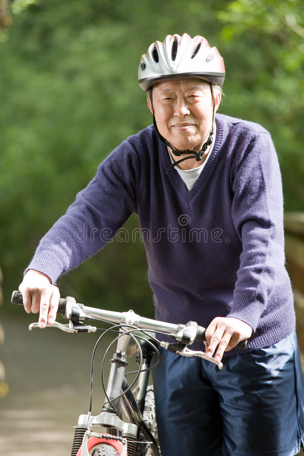 Biking sênior do asian imagens de stock