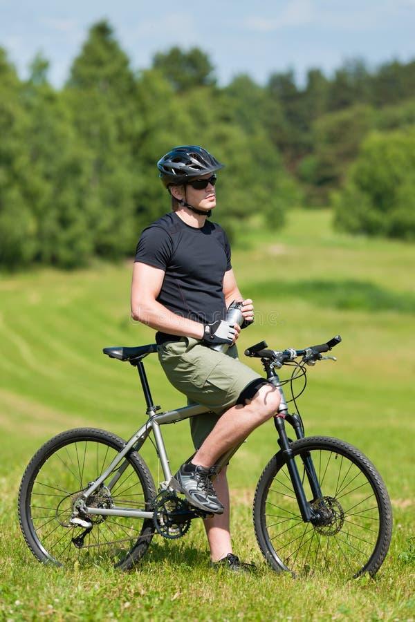 Biking Sportive da montanha do homem relaxa prados ensolarados foto de stock royalty free