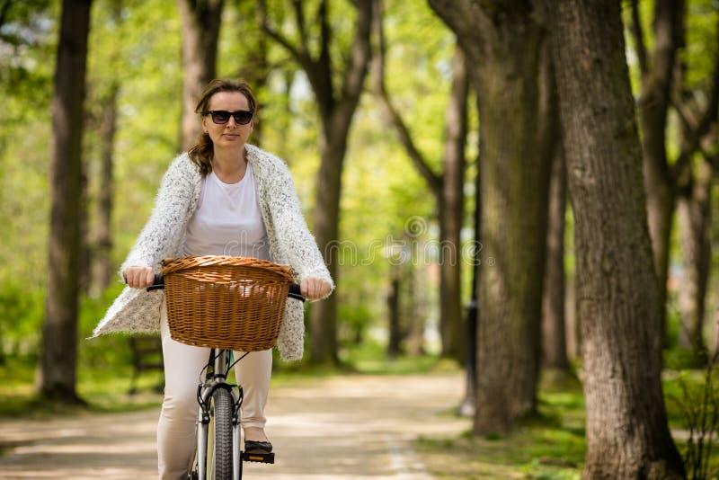 Biking urbano - bicicleta da equitação da mulher fotografia de stock royalty free