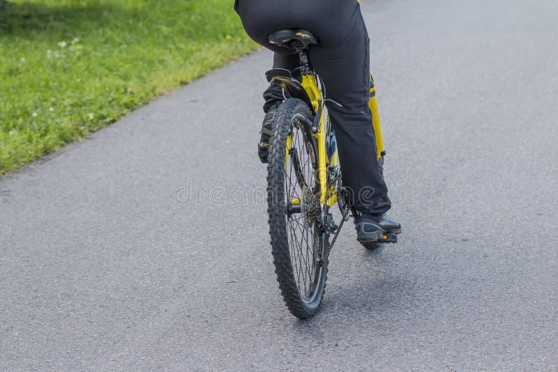 Biking urbano - homem e bicicleta na cidade equipe a montada de uma bicicleta na estrada asfaltada, vista da parte traseira Estil fotos de stock royalty free
