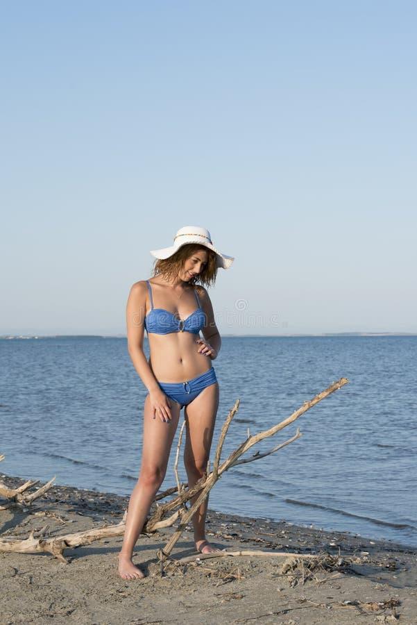 Bikini azul rubio del desgaste de mujer y sombrero blanco que se colocan en el mar imagenes de archivo