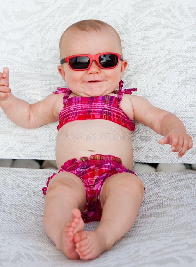 Bikini baby. Baby girl with sunglasses smiling in pink bikini royalty free stock photography