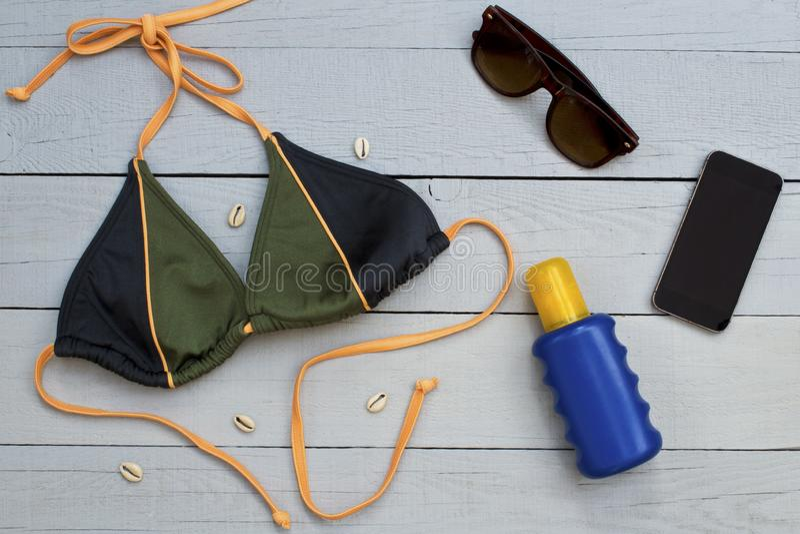 Bikini, bruine kleurroom, zonnebril en mobiele telefoon op houten achtergrond stock foto's