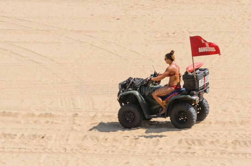 Bikini-clad Lifeguard drives a dune buggy at Virginia Beach, VA. Virginia Beach, VA-August 31, 2017: Lifeguard wearing a bikini drives a dune buggy at Virginia royalty free stock images