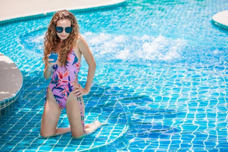 bikini d'uso della bella giovane donna sexy con gli occhiali da sole che bevono cocktail nella piscina Ragazza graziosa in costum fotografia stock libera da diritti