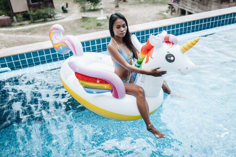 Bikini d'uso della donna asiatica sexy e rilassarsi sull'unicorno in una piscina immagini stock libere da diritti