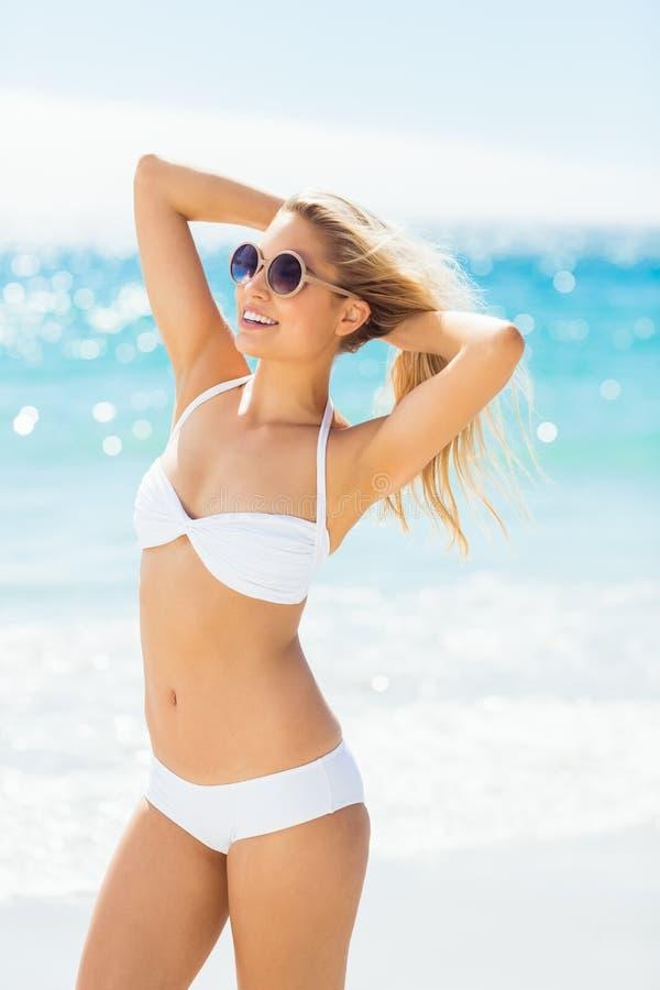 Bikini d'uso della donna che posa con gli occhiali da sole immagine stock libera da diritti
