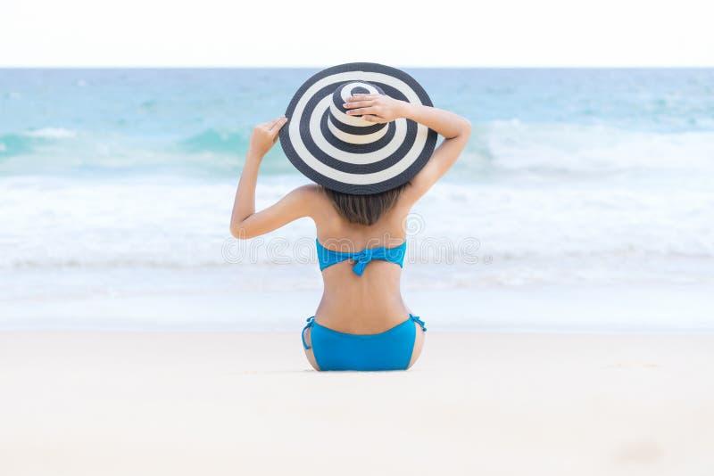Bikini d'uso della giovane bella donna sexy e rilassarsi sulla spiaggia sabbiosa bianca vicino alle onde del blu sulla spiaggia t immagini stock