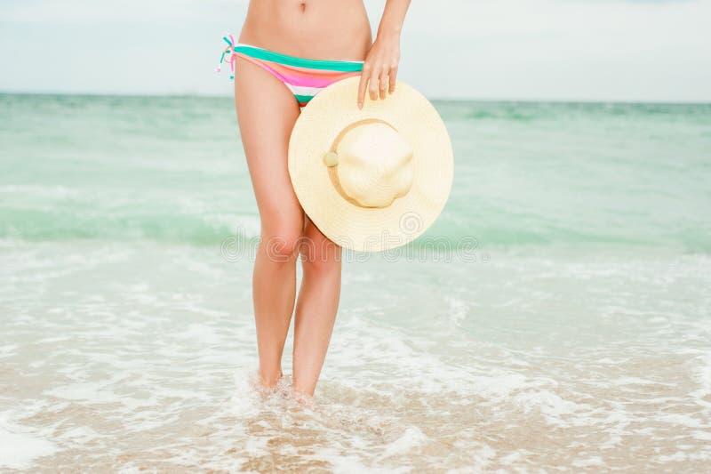 Bikini d'uso della ragazza e tenere un cappello di paglia fotografia stock