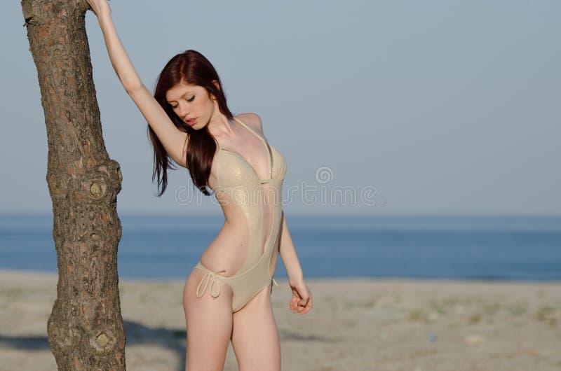 Bikini de la bata de la mujer roja joven atractiva del pelo que lleva fotos de archivo libres de regalías