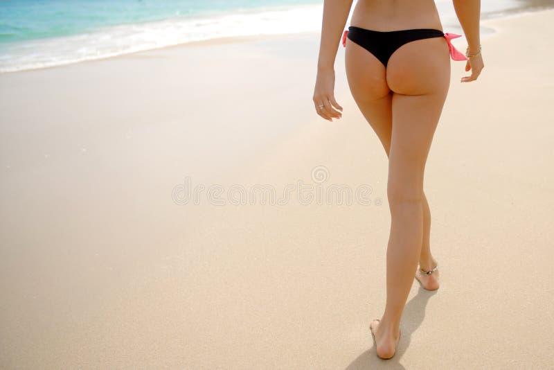 Bikini de port de lanière de femme marchant sur la plage image stock