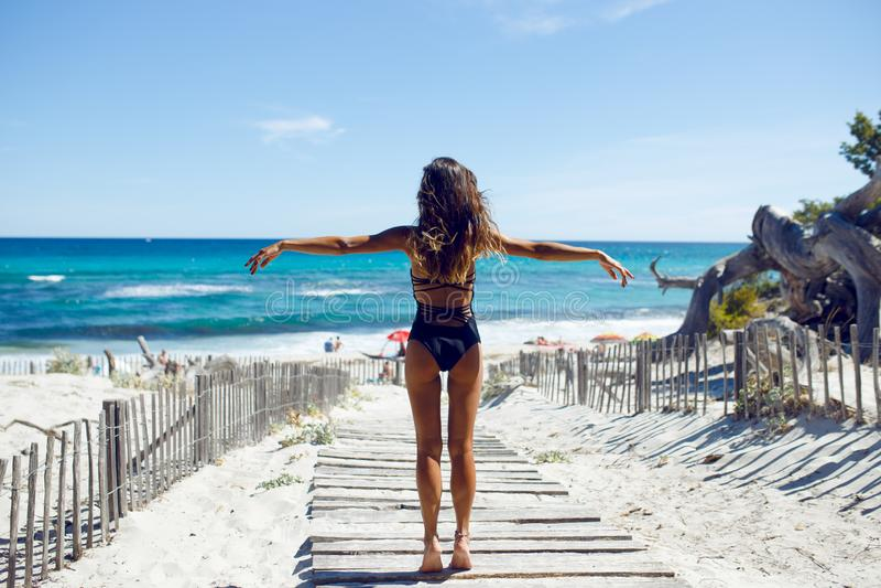 Bikini de port de femme sexy sur la plage La jeune femelle dans le maillot de bain se tenant sur le bord de la mer avec ses mains photos stock