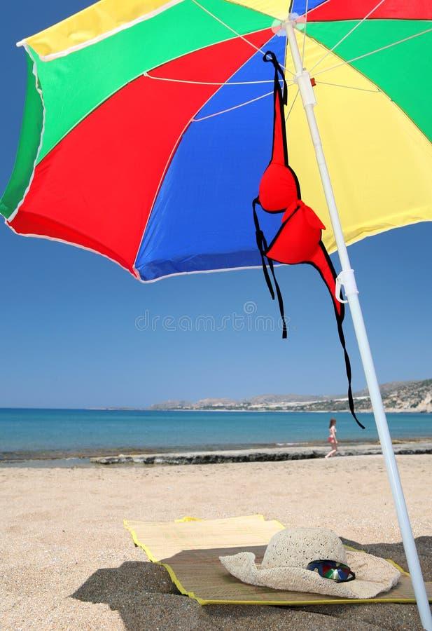 Bikini ed occhiali da sole del cappello della stuoia dell'ombrello di spiaggia immagine stock