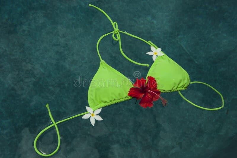 Bikini floating with pumleria and hibiscus flowers stock photos