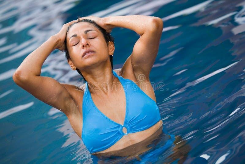 Bikini girl in pool stock photography