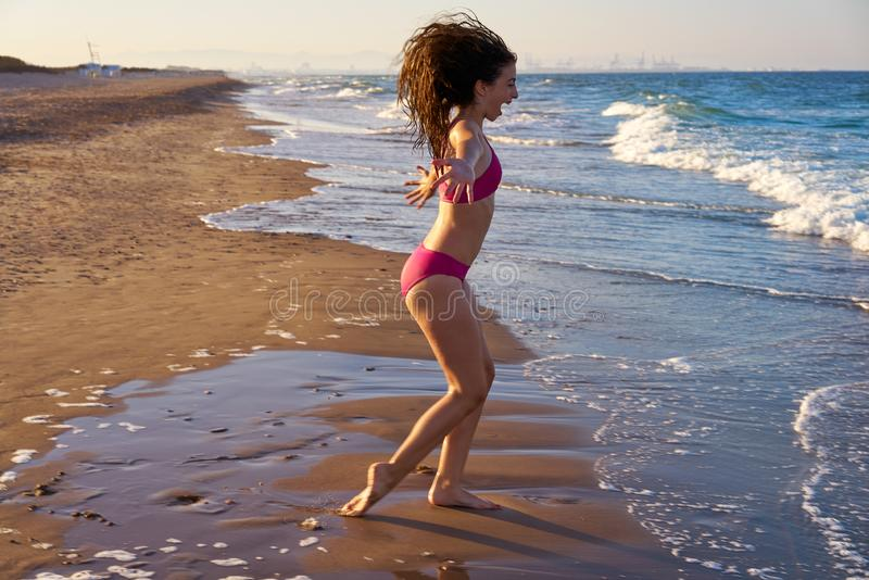 Bikini girl running to the beach shore water royalty free stock images