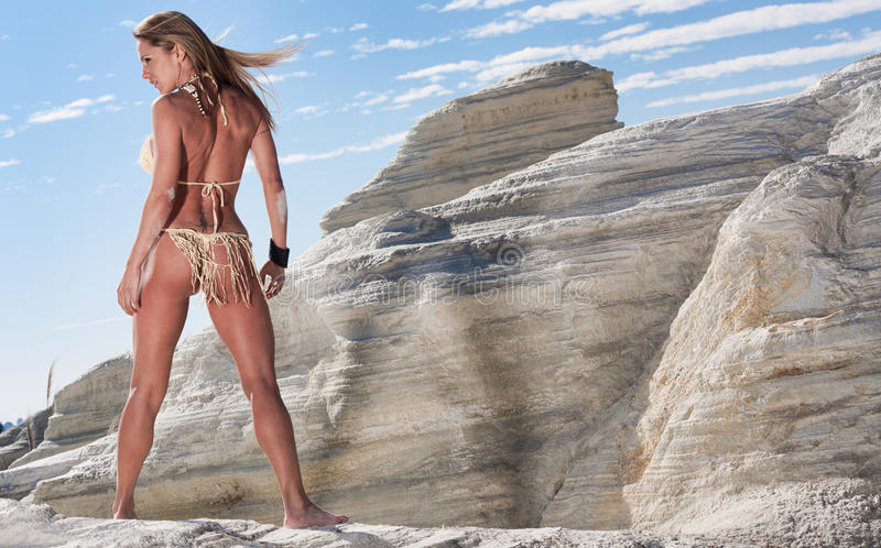 Bikini model. Shot from behind, a blond female model wearing a string bikini stands outside in a rocky summer landscape stock photography