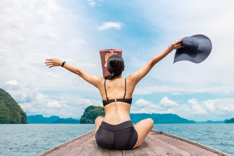 Bikini que lleva de la mujer que se sienta en el barco con las manos para arriba y que lleva a cabo el beachhat fotos de archivo libres de regalías