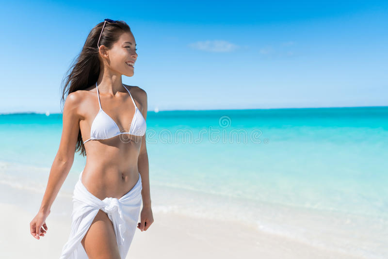 Bikini vacation woman relaxing in beach wear. Bikini woman relaxing in white sun protection beachwear walking on tropical Caribbean beach with turquoise ocean stock photography