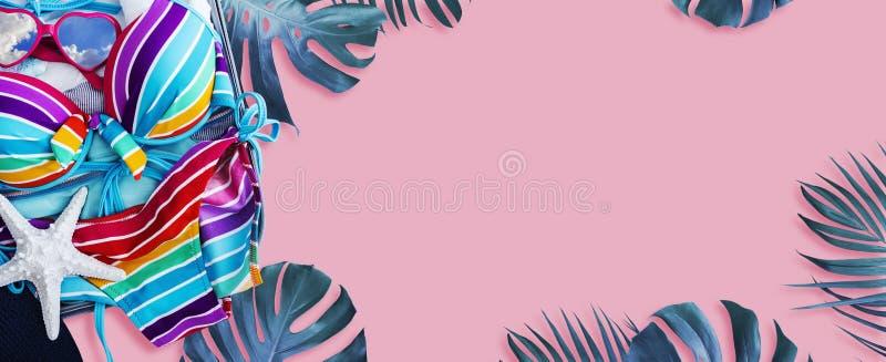 Bikini variopinto e vestiti in bagagli con le foglie tropicali fotografie stock